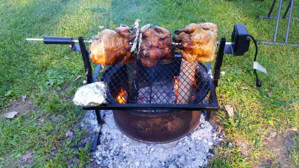Image of three chickens cooking on a spit over an open fire