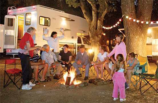 Image of family gathered around fire in front of their camper