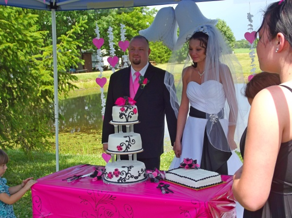 Image of bride & groom standing behind wedding cake