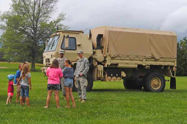 Another image of army transport truck being shown to children