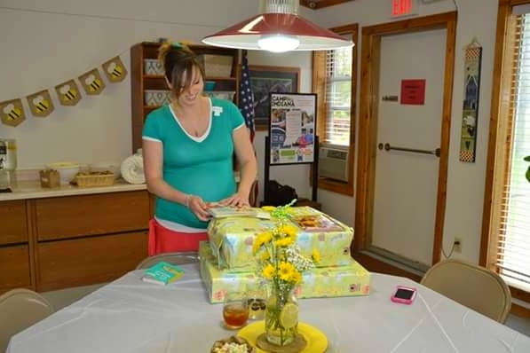 Image of mother opening baby shower gifts