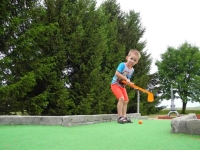 Image of little boy playing mini golf